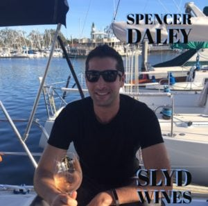 Spencer Daley drinking wine on a boat